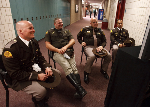 Leah Hogsten  |  The Salt Lake Tribune Utah Highway Patrol Troopers Josh Porter,  Jeff Stevens, Lt. Steve Winward and Phil Arnold laugh as they watch a monitor in the hallway of Northridge High School as family and co-workers deliver their tribute to Trooper Aaron Beesley.