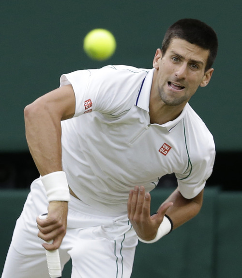 Novak Djokovic of Serbia serves to Roger Federer of Switzerland during a men's semifinals match at the All England Lawn Tennis Championships at Wimbledon, England, Friday, July 6, 2012. (AP Photo/Kirsty Wigglesworth)