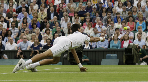 Novak Djokovic of Serbia misses a return to Roger Federer of Switzerland during a semifinals match at the All England Lawn Tennis Championships at Wimbledon, England, Friday, July 6, 2012. (AP Photo/Anja Niedringhaus)