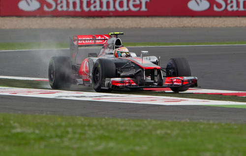 Britain's Lewis Hamilton driving a McLaren-Mercedes Formula 1 car takes a wide line through Luffield corner during practice at the Silverstone circuit, England, Saturday, July 7, 2012. The Formula 1 teams make preparations ahead of the British Grand Prix at Silverstone circuit on Sunday. (AP Photo/Tom Hevezi)