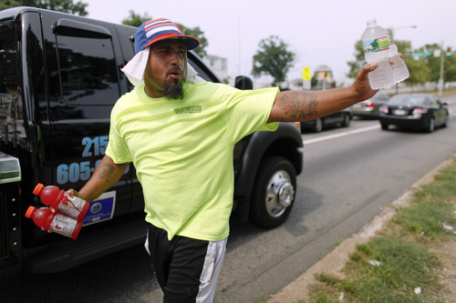 Frank Moralez sells cold beverages to motorists on the Roosevelt Boulevard, Saturday, July 7, 2012, in the Feltonville section of Philadelphia. Temperatures of more than 100 degrees were forecast in Philadelphia and excessive heat warnings were issued for several states in the Midwest as a heat wave continued. (AP Photo/Joseph Kaczmarek)