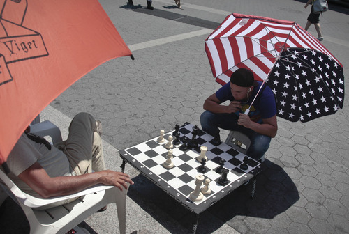 Luis Saavevra shades from the heat with a giant U.S. flag umbrella as he plays chess on an over-sized board in Union Square as temperature reached the 90s  on Friday, July 6, 2012 in New York. he National Weather Service reported late Thursday that the record-breaking heat that has baked the nation's midsection for several days was slowly moving into the mid-Atlantic states and Northeast.  (AP Photo/Bebeto Matthews)