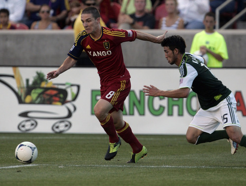 Kim Raff | The Salt Lake Tribune Real Salt Lake player Will Johnson dribbles past Portland Timbers player Kosuke Kimura at Rio Tinto Stadium in Sandy, Utah on July 7, 2012. Real went on to win the game 3-0.