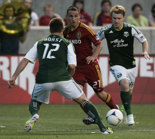 Kim Raff | The Salt Lake Tribune Real Salt Lake player Luis Gil passes around Portland Timbers defender David Horst at Rio Tinto Stadium in Sandy, Utah on July 7, 2012.  Real went on to win the game 3-0.