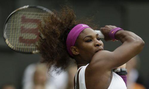 Serena Williams of the United States plays a shot to Agnieszka Radwanska of Poland during the women's final match at the All England Lawn Tennis Championships at Wimbledon, England, Saturday, July 7, 2012. (AP Photo/Alastair Grant)