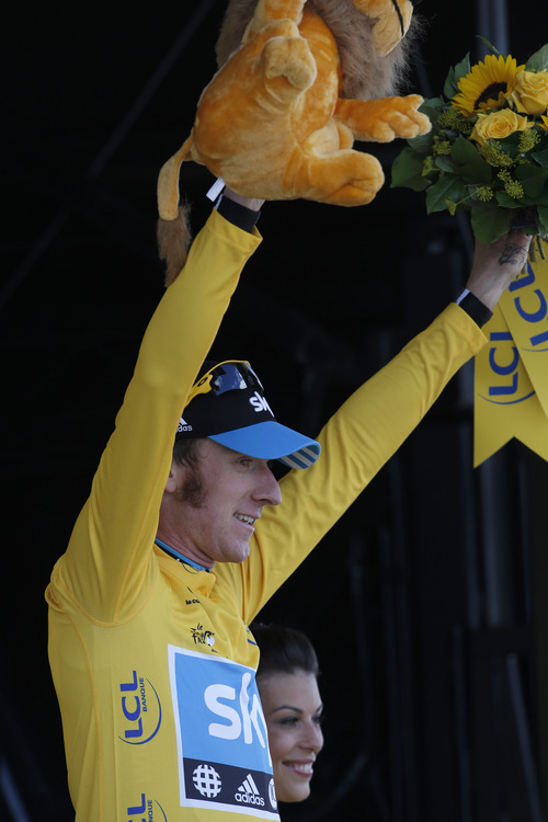 Bradley Wiggins of Britain, wearing the overall leader's yellow jersey, celebrates on the podium of the 8th stage of the Tour de France cycling race over 157.5 kilometers (98.5 miles) with start in Belfort, France, and finish in Porrentruy, Switzerland, Sunday July 8, 2012. (AP Photo/Laurent Rebours)
