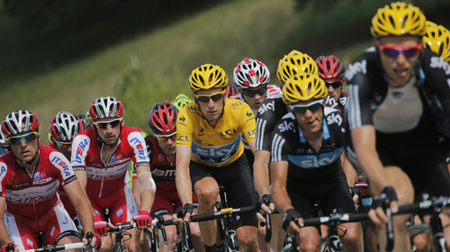 The pack with Denis Menchov of Russia, second left, Cadel Evans of Australia, behind Bradley Wiggins of Britain, wearing the overall leader's yellow jersey, ride in the pack during the 8th stage of the Tour de France cycling race over 157.5 kilometers (98.5 miles) with start in Belfort, France, and finish in Porrentruy, Switzerland, Sunday July 8, 2012. (AP Photo/Christophe Ena)