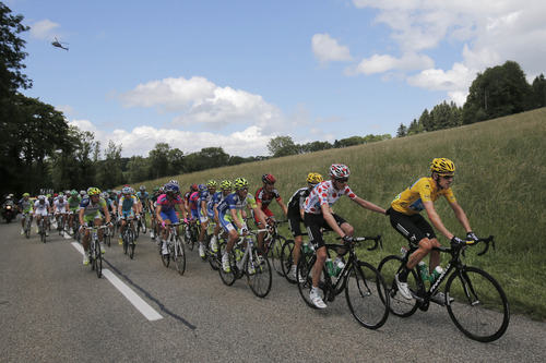Christopher Froome of Britain, wearing the best climber's dotted jersey, pushes teammate Bradley Wiggins of Britain, wearing the overall leader's yellow jersey, as they climb Cote de Saignelegier during the 8th stage of the Tour de France cycling race over 157.5 kilometers (98.5 miles) with start in Belfort, France, and finish in Porrentruy, Switzerland, Sunday July 8, 2012. (AP Photo/Christophe Ena)