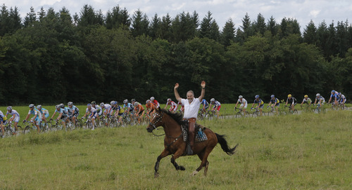 A man rides his horse alongside the pack during the 8th stage of the Tour de France cycling race over 157.5 kilometers (98.5 miles) with start in Belfort, France, and finish in Porrentruy, Switzerland, Sunday July 8, 2012. (AP Photo/Laurent Cipriani)