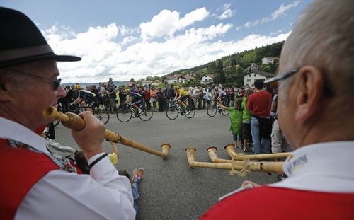 Traditional Swiss horn blowers are seen in the foreground as the pack with Bradley Wiggins of Britain, wearing the overall leader's yellow jersey, passes during the 8th stage of the Tour de France cycling race over 157.5 kilometers (98.5 miles) with start in Belfort, France, and finish in Porrentruy, Switzerland, Sunday July 8, 2012. (AP Photo/Laurent Cipriani)