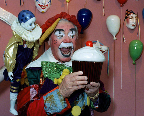 FILE - In this June 18, 1985, file photo, Ernest Borgnine holds a giant cupcake dressed as a clown in Los Angeles, for the revival of the Great Circus Parade in Milwaukee.  A spokesman said Sunday, July 8, 2012, that Borgnine has died at the age of 95. (AP Photo/Robert Gabriel, File)