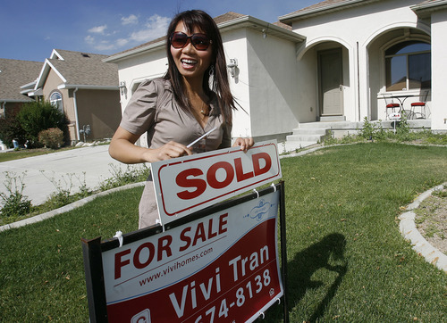 Scott Sommerdorf  |  The Salt Lake Tribune              Vivi Tran, a Realtor, is second vice chairman of the Utah Vietnamese American Chamber of Commerce. She adds a SOLD sign to a sign outside a home in West Valley City she has just sold, Friday June 29, 2012.