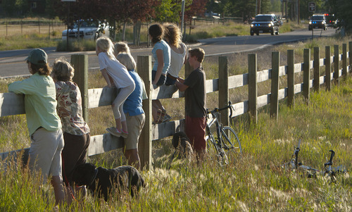 Steve Griffin | The Salt Lake Tribune   People sit on a wood fence as the motorcade of the Vice President of the United States,  Joe Biden, passes them on the Old Ranch Road in Park City, Utah Tuesday July 10, 2012. Bidden was speaking at a fundraiser at the Park City home of John and Kristi Cumming.