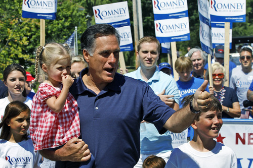 Charles Dharapak  |  The Associated Press Republican presidential candidate Mitt Romney gives a thumbs up as he carries his granddaughter Soleil while walking in the Fourth of July Parade in Wolfeboro, N.H., Wednesday, July 4, 2012.