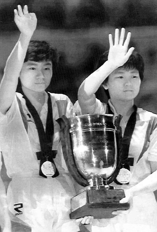In this April 30, 1991 photo, South Korea's Hyun Jung-hwa, left, and North Korea's Ri Bun Hui, Koreas' first-ever unified team, wave while holding their winning trophy after they defeated China at a world table tennis championships competition in Chiba, Japan. Grudgingly putting aside politics, the intensely competitive Ri paired up with her arch rival, South Korean star Hyun, in 1991 as part of the first