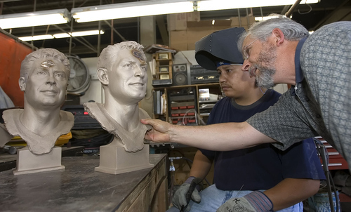 Welder Richardo Flores, left, and sculptor Blair Buswell look for flaws to be corrected in the bronze bust of Steve Young at the Adonis Bronze Foundry in Alpine in July 2005. Flores, 41, of Pleasant Grove, died Thursday in an explosion at the factory. (Photo by George Frey).