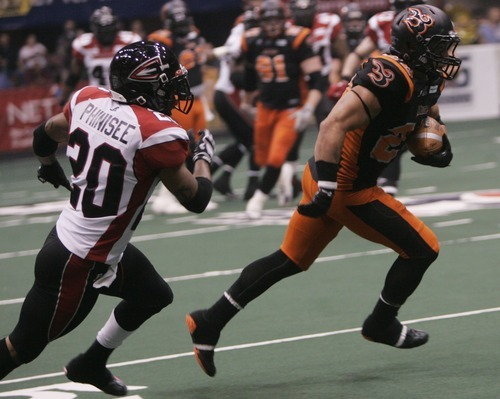 Kim Raff | The Salt Lake Tribune Utah Blaze plaer Aaron Lesue makes a run down the field as Cleveland Gladiators player Joe Phinisee trails behind during a game at the EnergySolutions Arena in Salt Lake City, Utah on July 13, 2012.