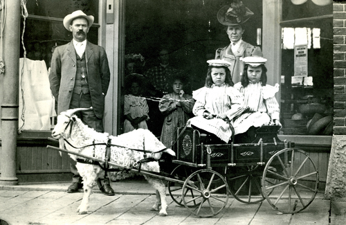 John W. Tolton and wife strolling with their daughters along Main Street.