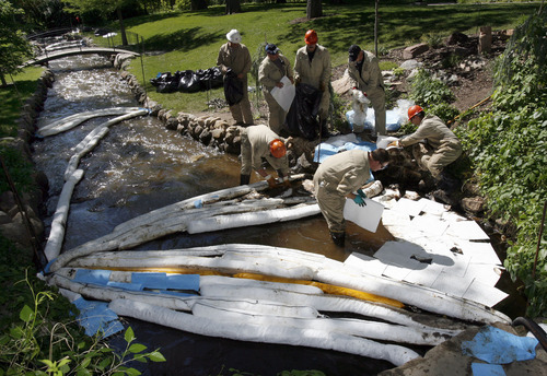 Francisco Kjolseth  |  Tribune file photo Crews try and clean up the oil spill flowing down Red Butte Creek through Garden Park LDS Ward on June 14, 2010, after water drained from the small pond pushed more oil through.