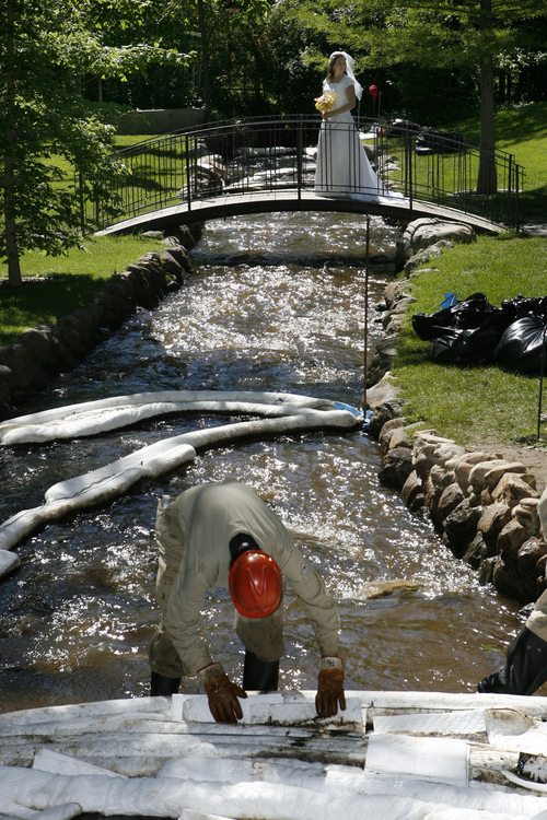Francisco Kjolseth  |  Tribune file photo Crews try to clean up the oil spill flowing down Red Butte creek through Garden Park LDS Ward in Salt Lake where Erin Swensen was getting her bridal photos taken despite the oily mess in 2010.