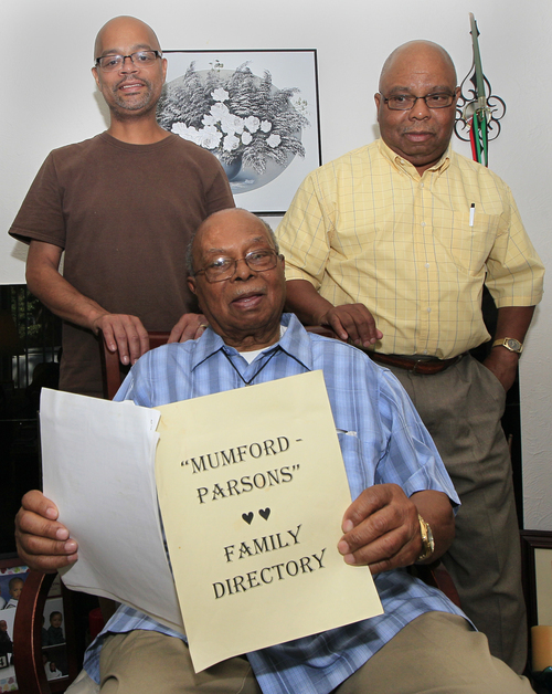 In this Monday, June 25, 2012 photo, Jewell Wilson, foreground, great-grandson of former slave Jordan Anderson, holds a family directory as he poses with his son Jewell Wilson Jr., left, and his nephew Barry Mumford Wilson, in Dayton, Ohio. Anderson, who wrote a remarkable letter to his ex-master, was freed from a Tennessee plantation by Union troops in 1864 and spent his remaining 40 years in Ohio. (AP Photo/Al Behrman)