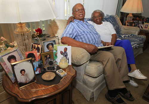 In this Monday, June 25, 2012 photo, Jewell Wilson, great-grandson of former slave Jordan Anderson, is flanked by photos of family members as he sits with his wife, Estella Wilson, at their home in Dayton, Ohio. Anderson, who wrote a remarkable letter to his ex-master, was freed from a Tennessee plantation by Union troops in 1864 and spent his remaining 40 years in Ohio. (AP Photo/Al Behrman)
