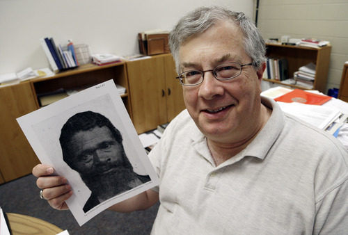 In this Wednesday, June 27, 2012 photo, Roy Finkenbine, University of Detroit Mercy History Professor and Interim Dean, College of Liberal Arts and Education, holds a print showing Jordan Anderson, in his office in Detroit. Finkenbine is planning a biography of the former slave who is credited with writing a remarkable letter to his ex-master. (AP Photo/Paul Sancya)