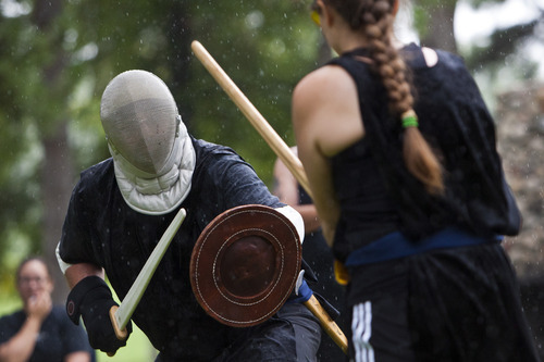 Chris Detrick  |  The Salt Lake Tribune Using a Viking short sword and buckler, Darrell Armstrong, of West Valley City, competes against Heather Rentz, of Holladay, and her great sword, during the United Clans Swordsman Association sword fighting competition at Liberty Park Saturday July 14, 2012. Twelve people competed in the twice-yearly event.