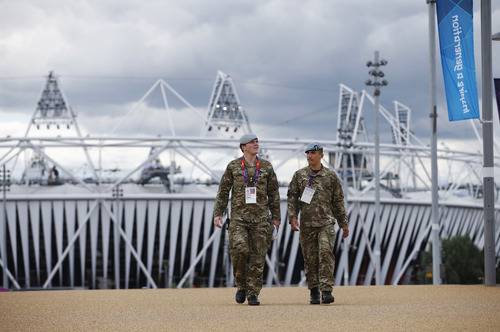British military personnel walk away from the Olympic Stadium as preparations continue for the 2012 Summer Olympics, Sunday, July 15, 2012, in London. (AP Photo/Jae Hong)