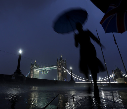 A pedestrian walks in the rain past the Tower Bridge displaying the Olympic rings, Saturday, July 14, 2012, as London prepares for the 2012 Summer Olympics in London. (AP Photo/Charlie Riedel)