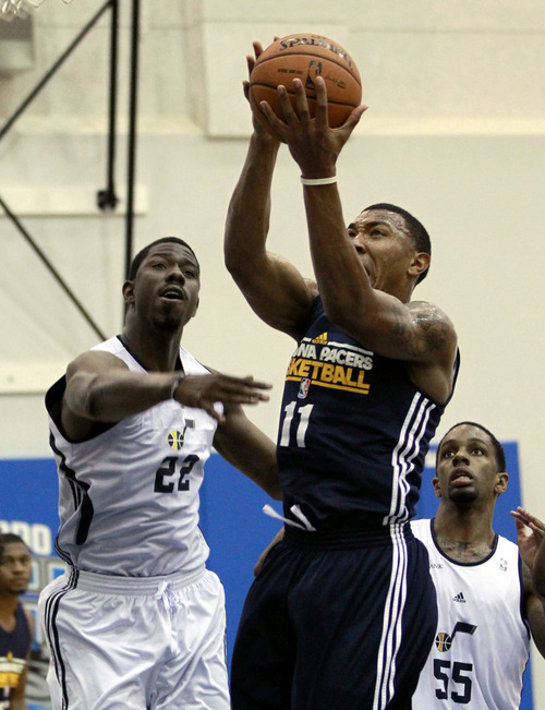 Indiana Pacers' Orlando Johnson (11) gets past Utah Jazz's Henry Sims (22) and Kevin Murphy (55) for a shot during an NBA summer league basketball game, Thursday, July 12, 2012, in Orlando, Fla. (AP Photo/John Raoux)