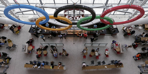 Patrons dine below the Olympic Rings at a coffee shot at Heathrow Airport, Tuesday, July 17, 2012 as London prepares for the 2012 Summer Olympics. (AP Photo/Charlie Riedel)