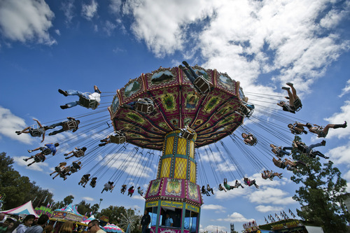 Every seat is filled on the The Wave Swinger ride at the Magical Midway at the California State Fair in Sacramento, Calif. on Tuesday, July 16 2012. (AP Photo/The Sacramento Bee, Manny Crisostomo)  MAGS OUT; TV OUT; MANDATORY CREDIT