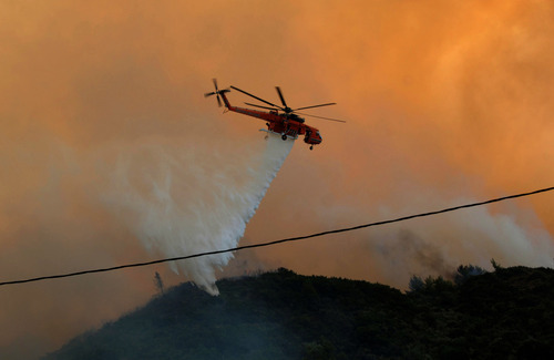An helicopter drops water over during an wild fire near Patras, Greece, Wednesday, July 18, 2012. Regional authorities declared an emergency in southwestern Greece as wildfires threatened village homes outside the city of Patras. Nine planes and one helicopter were involved in the firefighting effort Wednesday at Argyra, some 15 kilometers (9.3 miles) east of Patras, amid high winds and temperatures above 40 degrees Celsius (104 Fahrenheit). (AP Photo/Giannis Androutsopoulos)