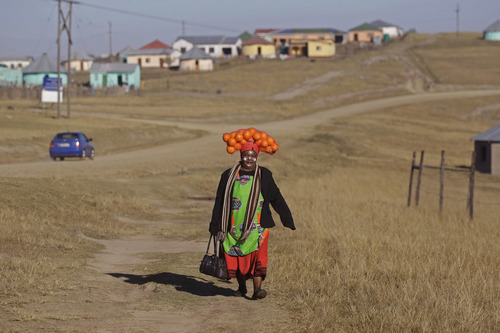 A woman carrying oranges on her head walks to a party in hounor of former South African President Nelson Mandela during celebrations for Mandela's birthday in Mvezo, South Africa, Wednesday, July 18, 2012. Across the country, and even abroad, people are doing good deeds to honor the country's most famous statesman on his 94th birthday today. (AP Photo/Schalk van Zuydam)