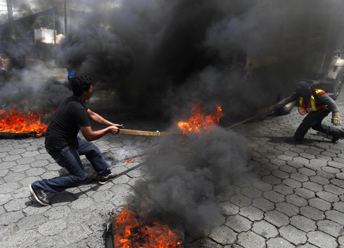 Members of Broad Opposition Front, FAO, civil organization, set on fire a vehicle belonging to Managua's town council during a protest in front of the Supreme Electoral Council, CSE, in Managua, Nicaragua, Tuesday, July 17, 2012. Demonstrators protested against members of the Supreme Electoral Council and demanded fairness and transparency in the upcoming November 7 municipal elections. (AP Photo/Esteban Felix)