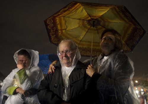 Relatives of victims attend a memorial ceremony marking the five-year anniversary of a plane crash at the site of the tragedy in Sao Paulo, Brazil, Tuesday, July 17, 2012. An aircraft of Brazil's TAM airline crashed and burst into flames in Sao Paulo, July 17, 2007, after skidding off a runway that had been criticized as being too short, in a driving rain, killing at least 199 people. (AP Photo/Andre Penner)