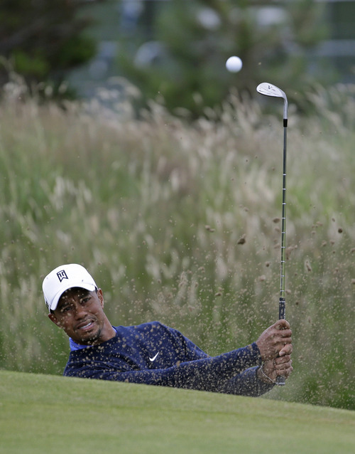 Tiger Woods of the United States plays from a bunker on the 12th hole during a practice round at Royal Lytham & St Annes golf club ahead of the British Open Golf Championship, Lytham St Annes, England, Tuesday, July  17, 2012. (AP Photo/Tim Hales)