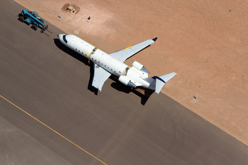 A SkyWest regional jet sits on the tarmac on the opposite end of the St. George Municipal Airport Tuesday, July 17, 2012.  A SkyWest Airlines employee wanted in a murder case attempted to steal a passenger plane, then shot himself in the head after crashing the aircraft in a nearby parking lot, officials said Tuesday. Brian Hedglin, 40, scaled a razor wire fence at the St. George Municipal Airport early Tuesday, then boarded the 50-passenger SkyWest jet while the airport was closed, St. George city spokesman Marc Mortenson said.  (AP Photo/The Spectrum, Jud Burkett)
