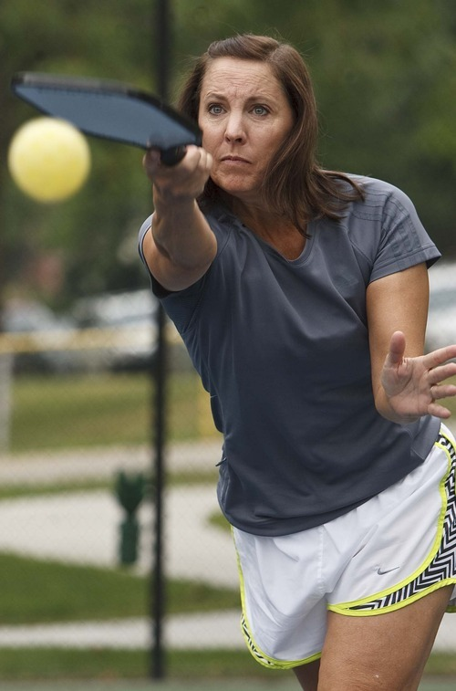 Leah Hogsten  |  The Salt Lake Tribune Laurel Schwendiman serves while playing pickleball. The popular game is played on a court with a lowered net with a perforated plastic baseball (similar to a whiffle ball) and wood or composite paddles. Salt Lake City has added pickleball courts to Reservoir Park due to the growing popularity of the sport.