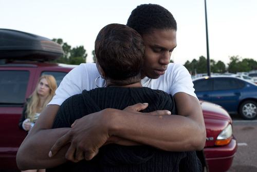 Eyewitness Isaiah Bow hugs his mother Shamecca Davis after being questioned by police outside Gateway High School where witnesses were brought in, Friday, July 20, 2012 in Aurora, Colo.  After leaving the theater Bow went back in to find his girlfriend.