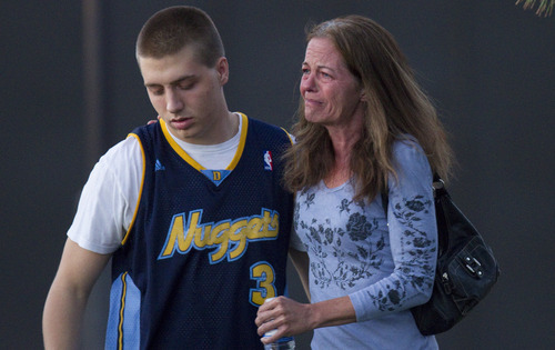 Eyewitness Jacob Stevens, 18, hugs his mother Tammi Stevens after being interview by police outside Gateway High School where witnesses were brought for questioning Friday, July 20, 2012 in Aurora, Colo.   A gunman wearing a gas mask set off an unknown gas and fired into the crowded movie theater killing 12 people and injuring at least 50 others, authorities said. (AP Photo/Barry Gutierrez)