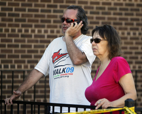 John Priest, left, and Vory Boots watch the police action at an apartment where the suspect in a theatre shooting lived in Aurora, Colo., on Friday, July 20, 2012. The couple were evacuated from their apartment across from the suspects.  As many as 12 people were killed and 50 injured at a shooting at the Century 16 movie theatre on Friday. The suspect is identified as 24-year-old James Holmes.  (AP Photo/Ed Andrieski)