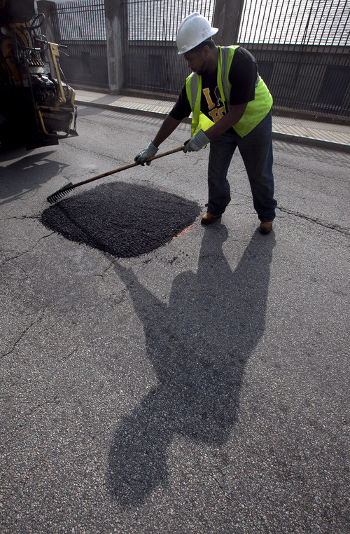 In this Thursday, July 19, 2012 photo Boston Public Works worker Tyrone Odom, of Boston, fills a pothole with asphalt in Boston's Charlestown neighborhood. Boston officials hope a new smartphone application could eventually eliminate the need to send out trucks to survey the hundreds of miles of roadways to figure out the locations of potholes.  (AP Photo/Steven Senne)