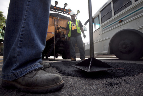 In this Thursday, July 19, 2012 photo Boston Public Works workers Victor Duret, feet only at left, and Tyrone Odom, behind, both of Boston, fill a pothole with asphalt in Boston's Charlestown neighborhood. Boston officials hope a new smartphone application could eventually eliminate the need to send out trucks to survey the hundreds of miles of roadways to figure out the locations of potholes.  (AP Photo/Steven Senne)