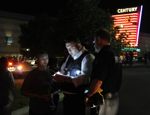 An Aurora Police Department detective takes a witness statement following a shooting Friday morning July 20, 2012. Aurora Police responded to the Century 16 movie theatre early Friday morning where police confirm at least 12 people are dead and 50 others injured. (AP Photo/Karl Gehring, The Denver Post)