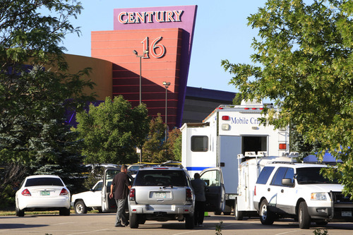 Police officers arrive at the Century 16 theatre east of the Aurora Mall in Aurora, Colo., on Friday, July 20, 2012.   A gunman wearing a gas mask set off an unknown gas and fired into the crowded movie theater killing 12 people and injuring at least 50 others, authorities said.  (AP Photo/David Zalubowski)