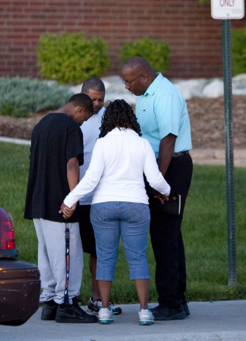 A small group prays outside Gateway High School where witness were brought for questioning Friday, July 20, 2012 in Aurora, Colo.  A gunman wearing a gas mask set off an unknown gas and fired into the crowded movie theater killing 12 people and injuring at least 50 others, authorities said. (AP Photo/Barry Gutierrez)