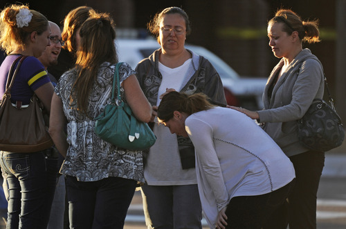 A group of friends are overcome with emotion as they gather outside Gateway High School, Friday July 20, 2012, in Aurora, Colo. They recieved news that their friend was killed during a shooting early Friday inside the Aurora movie theater.  A gunman wearing a gas mask set off an unknown gas and fired into the crowded movie theater killing 12 people and injuring at least 50 others, authorities said. (AP Photo/The Denver Post,  RJ Sangosti) TV, INTERNET AND MAGAZINES CALL FOR RATES AND TERMS