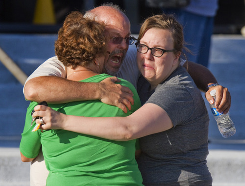 Tom Sullivan, center, embraces family members outside Gateway High School where he has been searching franticly for his son Alex Sullivan who celebrated his 27th birthday by going to see